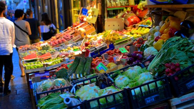 We shop in the medieval street market in Bologna's town center with fresh foods and vegetables.